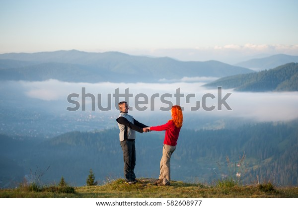 Happy pair holding hands and facing each other on a hill against beautiful mighty mountains and forests with morning haze in the valley