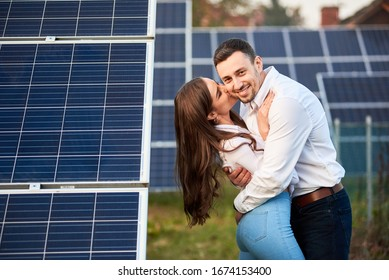 Happy pair are hugging against the background of a row of solar panels at a site near the house. Girl with long hair kisses a guy. Slender people in jeans and white shirts. Solar energy concept image