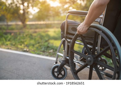 Happy Paralyzed,disabled or handicapped man in hope sitting relax on a wheelchair in nature park.Disabled handicapped man has a hope use smart phone for working,calling and searching for social media