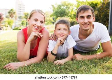 Happy parent with boy in teen age relaxing on green grass in park