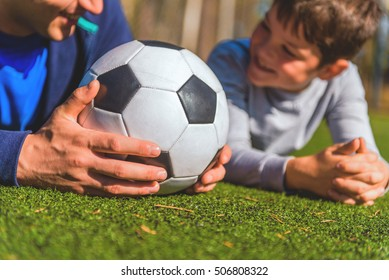 Happy parent and child are lying on lawn and smiling. Man is holding ball