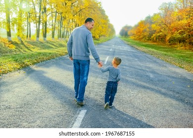Happy parent with child are walking along the road in the park on nature travel
