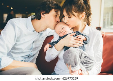 Happy parenthood: young parents kissing their sweet baby boy in cozy cafe interior.