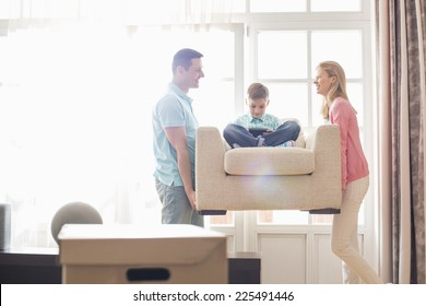 Happy parents carrying son on armchair in new house