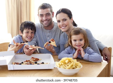 Happy parents and children eating pizza and fries at home