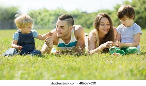 Happy parents with children laying  in  grass