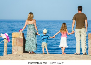 Happy parents with children playing on the sea background