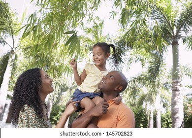 Happy parents with daughter enjoying together in park