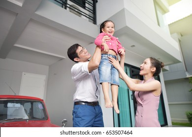 Happy parents with daughter in front of house