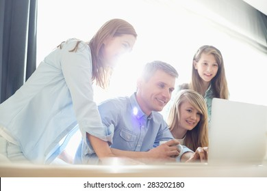 Happy parents with daughters using laptop at home