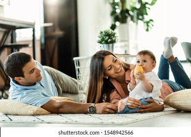 Happy parents enjoying in their time with their small son at home.