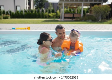 Happy parents. Happy good-looking parents feeling unbelievable swimming in pool with daughter