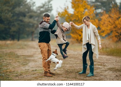 Happy parents have fun and lift up their daughter at forest path next to jumping dog during walk in autumn forest.