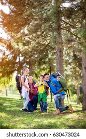 Happy parents hiking with their child in forest
