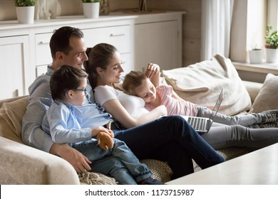 Happy parents hug kids lying on cozy sofa watching cartoons on laptop, young family spend time with children relaxing at home, mom and dad cuddle with son and daughter enjoying funny video at computer