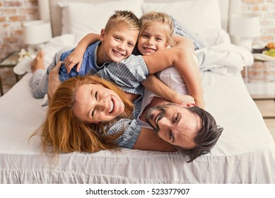 Happy parents and kids enjoying their morning in bed