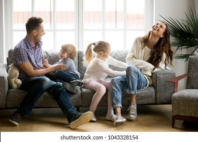 Happy parents and kids having fun tickling sitting together on sofa, cheerful couple laughing playing game with little active children son and daughter in living room at home, family funny activity