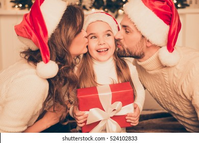 Happy parents kissing daughter and giving xmas present  on bed