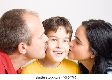 Happy parents kissing their son