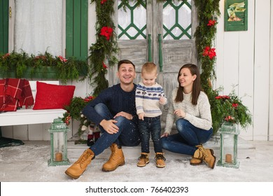 Happy parents with little son. Child boy in sweater sitting on porch snow steps at light house with decorated in red green New Year door at home. Christmas good mood. Family on holiday 2018 concept