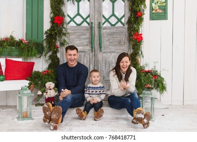 Happy parents with little son and petard. Child boy in sweater sitting on porch snow steps at light house with decorated in red green New Year door at home. Christmas good mood. Family on holiday