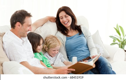 Happy parents looking at a photo album with their children on the sofa