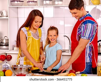 Happy parents  with nice daughter baking cookies.
