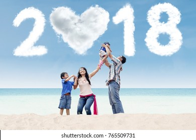 Happy parents playing with their children on the beach with clouds shaped numbers 2018 and heart in the sky