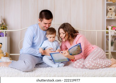 happy parents read a book your child in the nursery.