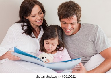Happy parents reading a story to their daughter in a bedroom