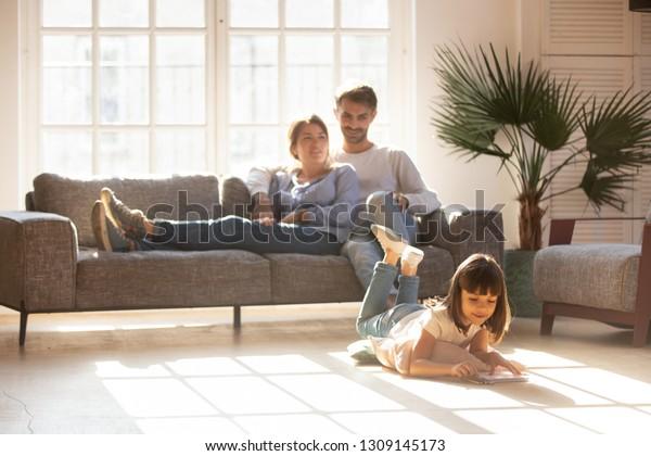 Fröhliche Eltern entspannen sich auf dem Sofa im komfortablen hellen Wohnzimmer, während kleine Kind Tochter auf warmen Boden mit farbigen Bleistiften spielen, Familie Spaß zusammen haben, Fußbodenheizung Konzept