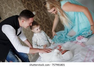 Happy parents show newborn son sister