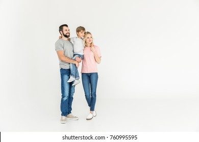 happy parents with son standing together and looking away isolated on white