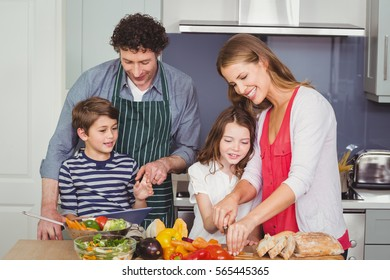 Happy parents standing with son and daughter in kitchen at home