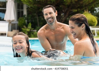 Happy parents teaching their daughter how to swim. Happy girl learning to swim in swimming pool. Smiling family playing with daughter in the swimming pool.