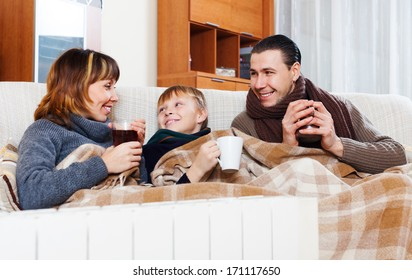 Happy parents and teenage son with cups of tea warming near warm calorifer in home