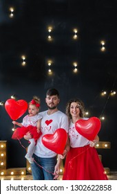 Happy parents and thair baby daughter on saint valentine's day. Parents with little kid with heart baloons. Vertical family portrait