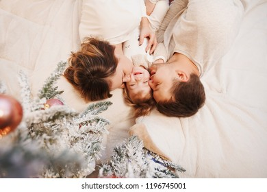 Happy parents and their baby 2 years old funny spend time under a Christmas tree. Happy Christmas holidays. Top view