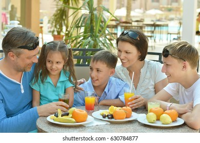 Happy parents with their children eating