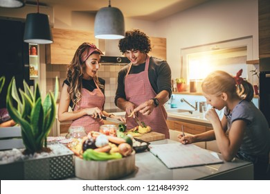 Happy parents and their daughter cooking together in the kitchen while little girl doing her homework on the kitchen table.