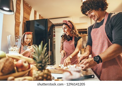 Happy parents and their daughter cooking together in the kitchen while little girl helping them.