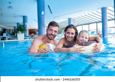 Happy parents with their daughter having fun in the swimming pool, summer vacation