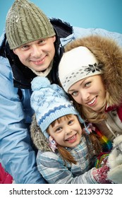 Happy parents and their daughter in winterwear looking at camera with smiles