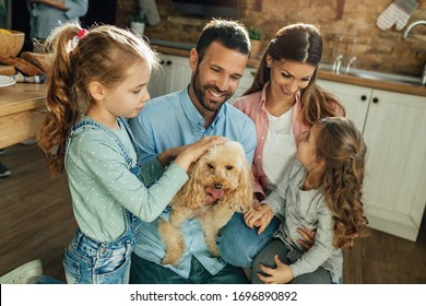 Happy parents and their daughters enjoying at home and having fun with their dog.