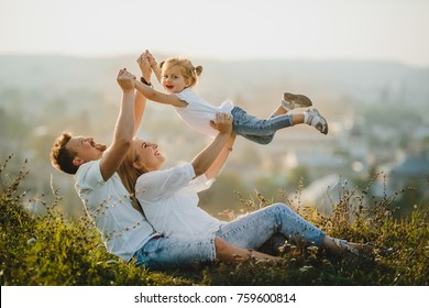 Happy parents and their little girl rest on the lawn in beautiful summer day