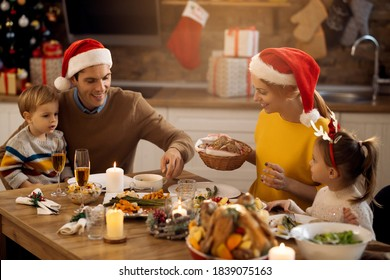 Happy parents and their small kids enjoying in Christmas lunch in dining room. Focus is on mother.
