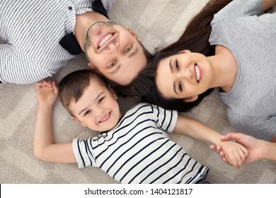 Happy parents and their son lying together on floor, view from above. Family time