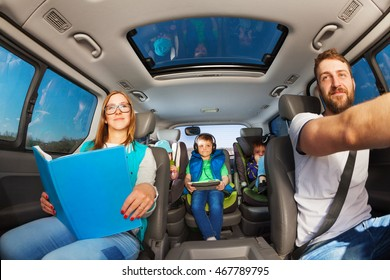 Happy parents traveling by car with kids