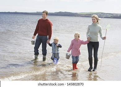 Happy parents with two children enjoying vacation on beach