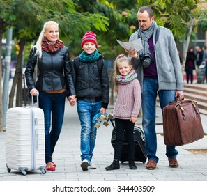 Happy parents with two kids and baggage using urban map